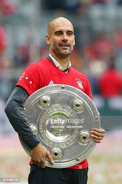Josep Guardiola the head coach of Bayern Muenchen celebrates with the trophy after winning the league during the Bundesliga match between FC Bayern...