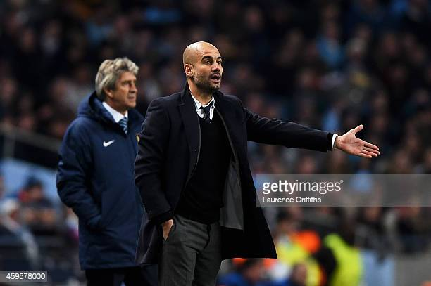 Josep Guardiola the head coach of Bayern Muenchen gestures as Manuel Pellegrini the manager of Manchester City looks on during the UEFA Champions...