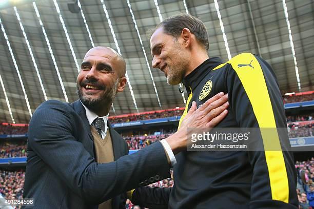 Josep Guradiola head coach of Muenchen shake hands with Thomas Tuchel head coach of Dortmund prior to the Bundesliga match between FC Bayern Muenchen...