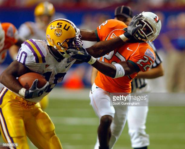 Joseph Addai of the LSU Tigers stiffarms Kelly Jennings of the Miami Hurricanes in the ChickFilA Peach Bowl on December 30 2005 at the Georgia Dome...