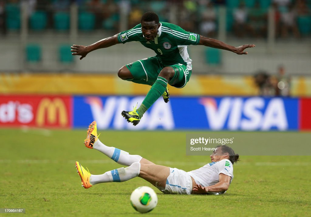 Joseph Akpala of Nigeria jumps a tackle from Martin Caceres of Uruguay during the FIFA Confederations Cup Brazil 2013 Group B match between Nigeria and Uruguay at Estadio Octavio Mangabeira (Arena Fonte Nova Salvador) on June 20, 2013 in Salvador, Brazil.