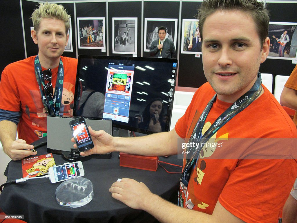 Joseph (L) and Sam Russell, brothers from Melbourne, Australia, show off their Jam smartphone app on March 14, 2013 at the South by Southwest (SXSW) festival in Austin, Texas. Jam enables users to sing into a smartphone, then add backing instruments and post the results for others to see and hear. AFP PHOTO / Robert MacPherson
