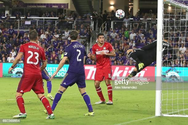 Joseph Bendik of Orlando City SC makes a save as Nemanja Nikolic of Chicago Fire Jonathan Spector of Orlando City SC and David Arshakyan of Chicago...