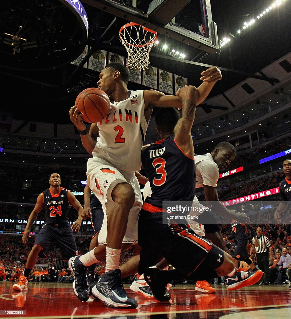 Joseph Bertrand #2 of the Illinois Fighting Illini gets tangled up while rebounding with Chris Denson #3 of the Auburn Tigers at United Center on December 29, 2012 in Chicago, Illinois. Illinois defeated Auburn 81-79.