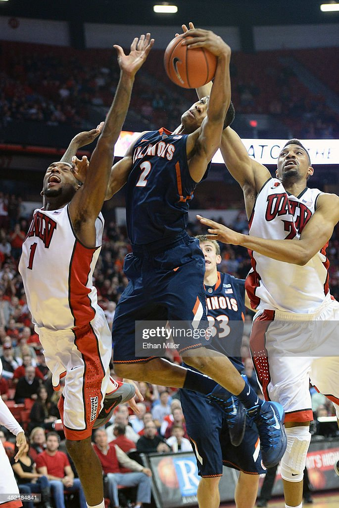 Joseph Bertrand #2 of the Illinois Fighting Illini grabs a rebound between Roscoe Smith #1 and Khem Birch #2 of the UNLV Rebels during their game at the Thomas & Mack Center on November 26, 2013 in Las Vegas, Nevada. Illinois won 61-59.