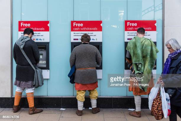 Joseph Bhart Jonny Graves19 and Matthew Clark dress as Vikings as they use cash machines in York city centre ahead of the 30th Viking Festival which...