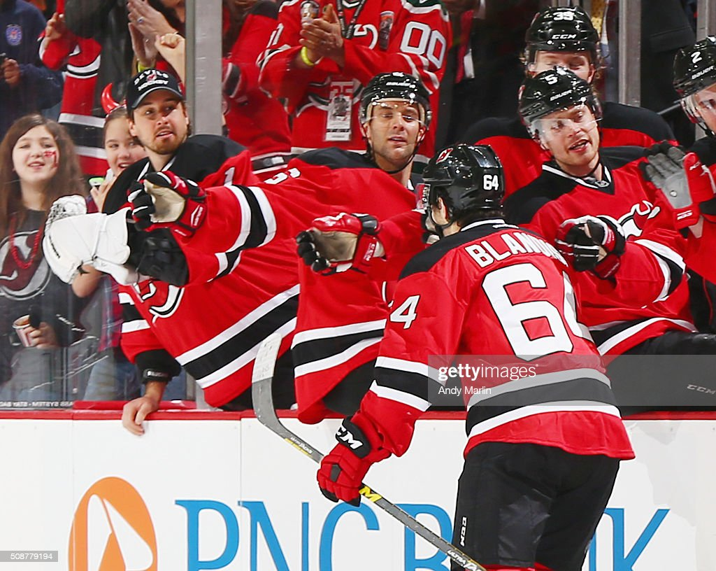 Joseph Blandisi #64 of the New Jersey Devils is congratulated his teammates after scoring a goal against the Washington Capitals at the Prudential Center on February 6, 2016 in Newark, New Jersey.