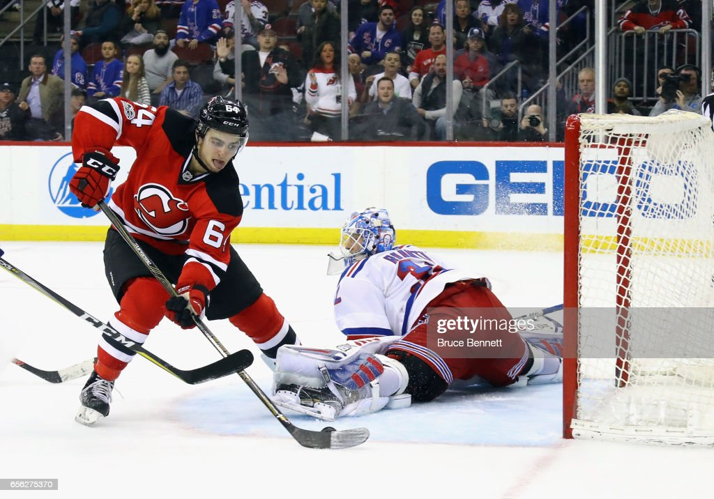 Joseph Blandisi #64 of the New Jersey Devils scores at 4:05 of overtime against Antti Raanta #32 of the New York Rangers at the Prudential Center on March 21, 2017 in Newark, New Jersey. The Devils defeated the Rangers 3-2 in overtime.