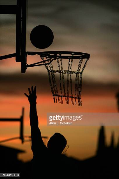 Joseph Carrillo of Santa Ana is silhouetted against a dramatic sunset while playing basketball at Mile Square Regional Park in Fountain Valley...