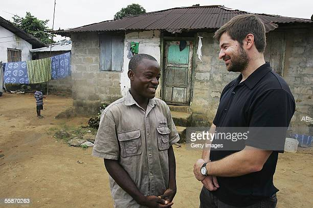 Joseph Duo a former Liberian government soldier talks with photographer Chris Hondros at his home October 5 2005 in Monrovia Liberia A picture of Duo...