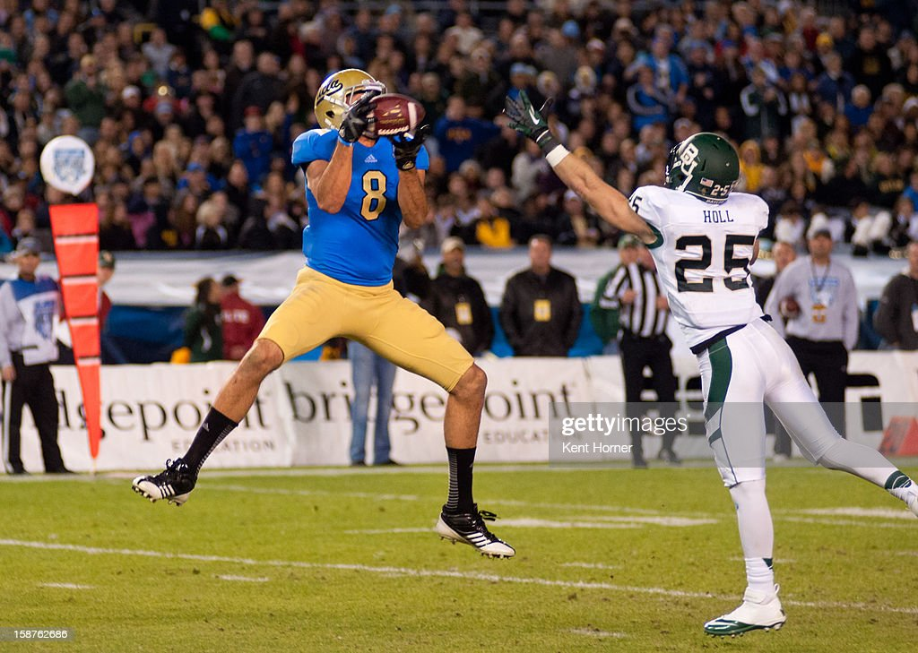 Joseph Fauria #8 of the UCLA Bruins leaps to catch the ball in the first half of the game against Sam Holl #25 of the Baylor Bears defends in the Bridgepoint Education Holiday Bowl at Qualcomm Stadium on December 27, 2012 in San Diego, California.