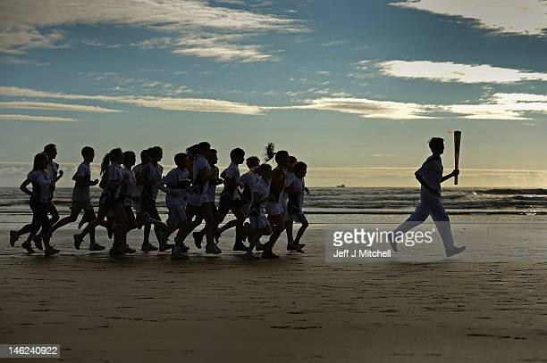 Joseph Forrest and children from Madras College run along West Sands with the Olympic Torch June 13 2012 in St Andrews Scotland The Olympic Flame is...