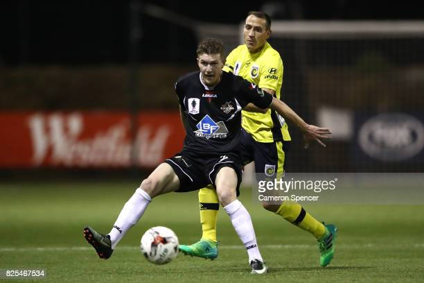 Joseph Gibbs of Blacktown City and Alan Baro of the Mariners contest the ball during the FFA Cup round of 32 match between Blacktown City and the...