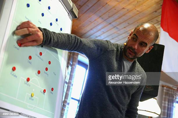 Joseph Guardiola head coach of FC Bayern Muenchen shows tactical moves on a tactics board during his visit to the FC Bayern Muenchen supporter club...