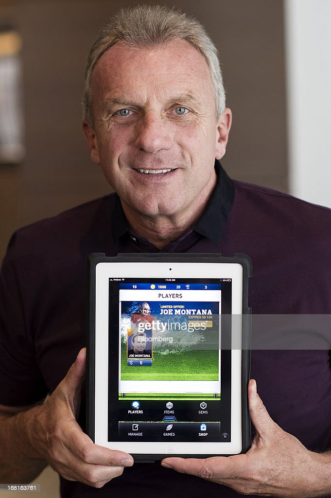 Joseph 'Joe' Montana, co-founder of iMFL and retired National Football League (NFL) quarterback, holds an Apple Inc. iPad with the iMFL game displayed as he sits for a photograph after an interview in San Francisco, California, U.S. on Tuesday, April 30, 2013. iMFL, a fantasy football application that will be available for download at the Apple Inc. App Store, will be released before the start of the 2013 NFL season. Photographer: David Paul Morris/Bloomberg via Getty Images