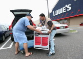 Joseph Klein of Sayville New York is assisted by Lowe's employee Ormani Rivera after his purchase of a generator as Hurrican Sandy approaches on...