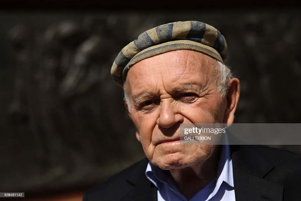 Joseph Kleinman, 86-year-old Israeli holocaust survivor who survived Auschwitz and Dachau Nazi death camps and lived to testify against Adolf Eichman, wears his hat from Auschwitz as he attends the annual Holocaust Remembrance Day ceremony at the Yad Vashem Holocaust Memorial in Jerusalem on May 5, 2016. The state of Israel marks the annual Memorial Day commemorating the six million Jews murdered by the Nazis in the Holocaust during World War II. / AFP / GALI