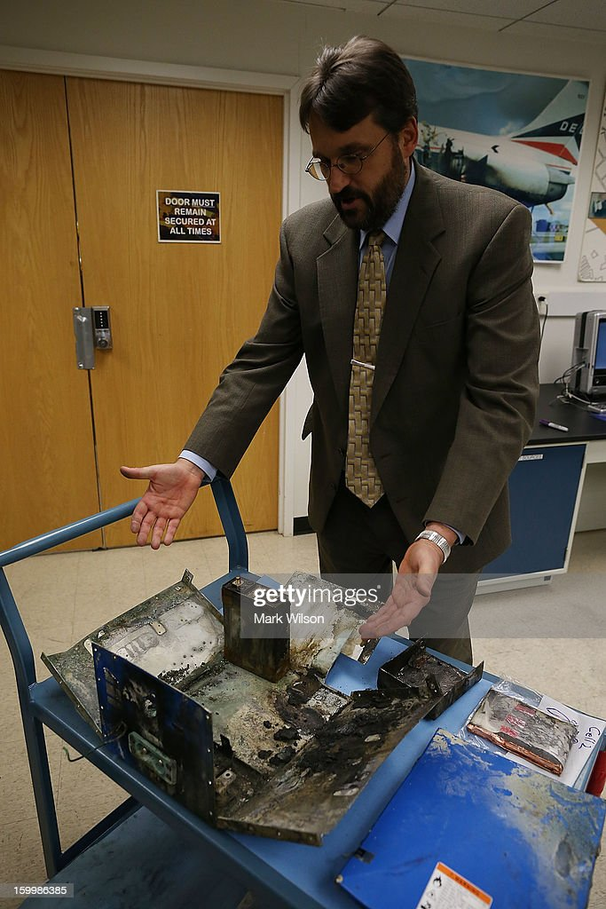 Joseph Kolly PH.D. of the National Transportation Safety Board displays the charred battery box from a Japan Airlines (JAL) 787 at the NTSB headquaters on January 24, 2013 in Washington, DC. The NTSB held a news conference to discuss the batteries that caused the January 7, fire aboard a Japan Airlines (JAL) Boeing 787 at Logan International Airport in Boston.