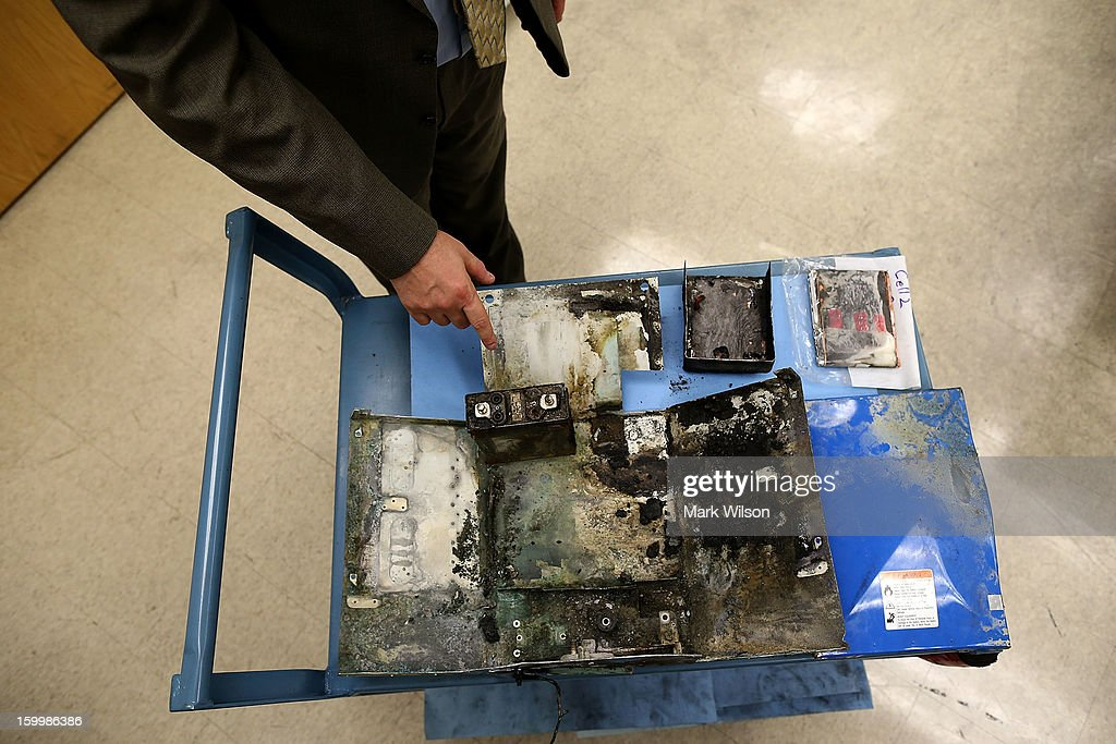 Joseph Kolly PH.D. of the National Transportation Safety Board shows the charred battery box from a Japan Airlines (JAL) 787 at the NTSB headquaters on January 24, 2013 in Washington, DC. The NTSB held a news conference to discuss the batteries that caused the January 7, fire aboard a Japan Airlines (JAL) Boeing 787 at Logan International Airport in Boston.