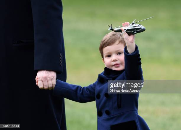 Joseph Kushner holds up a toy Marine One as his grandfather US President Donald Trump holds his hand when walking to board Marine One from the White...