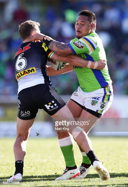 Joseph Leilua of the Raiders is tackled by Matt Moylan of the Panthers during the round 24 NRL match between the Canberra Raiders and the Penrith...