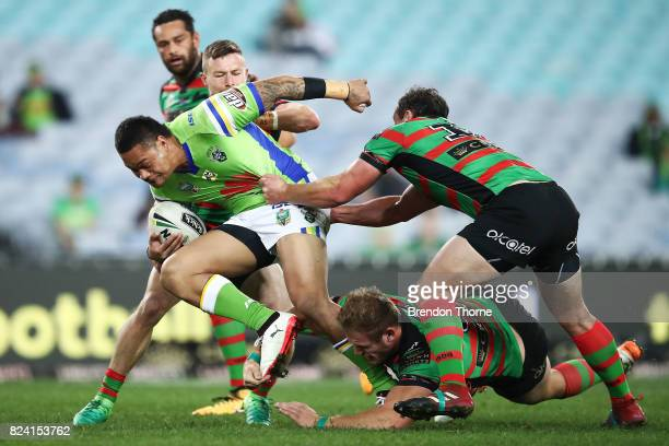 Joseph Leilua of the Raiders is tackled by the Rabbitohs defence during the round 21 NRL match between the South Sydney Rabbitohs and the Canberra...