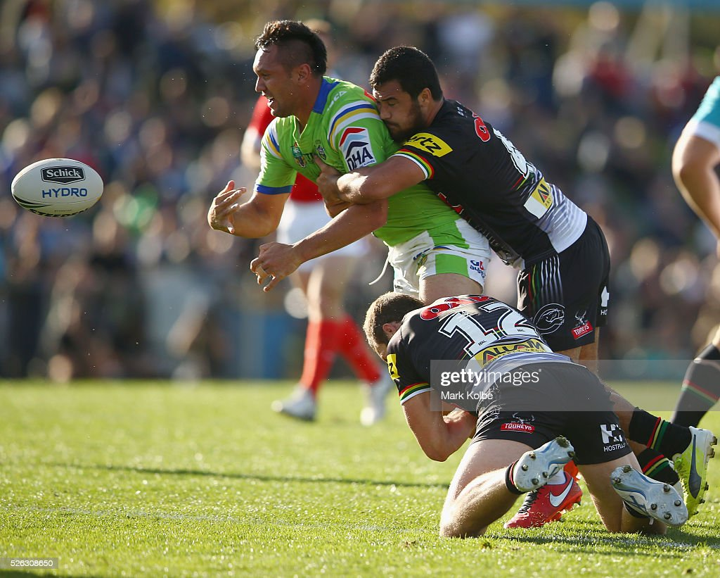 Joseph Leilua of the Raiders passes as he is tackled during the round nine NRL match between the Penrith Panthers and the Canberra Raiders at Carrington Park on April 30, 2016 in Bathurst, Australia.