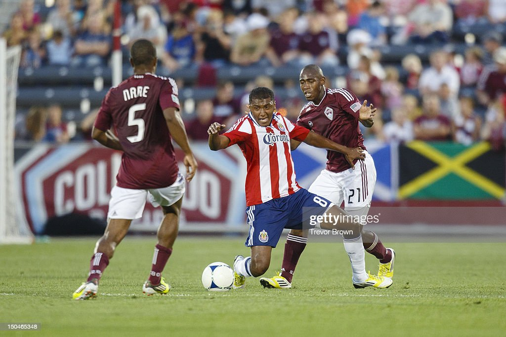 Joseph Nane and teammates Omar Cummings of Colorado Rapids battle with Oswaldo Minda of Chivas USA for possession of the ball during their MLS match...