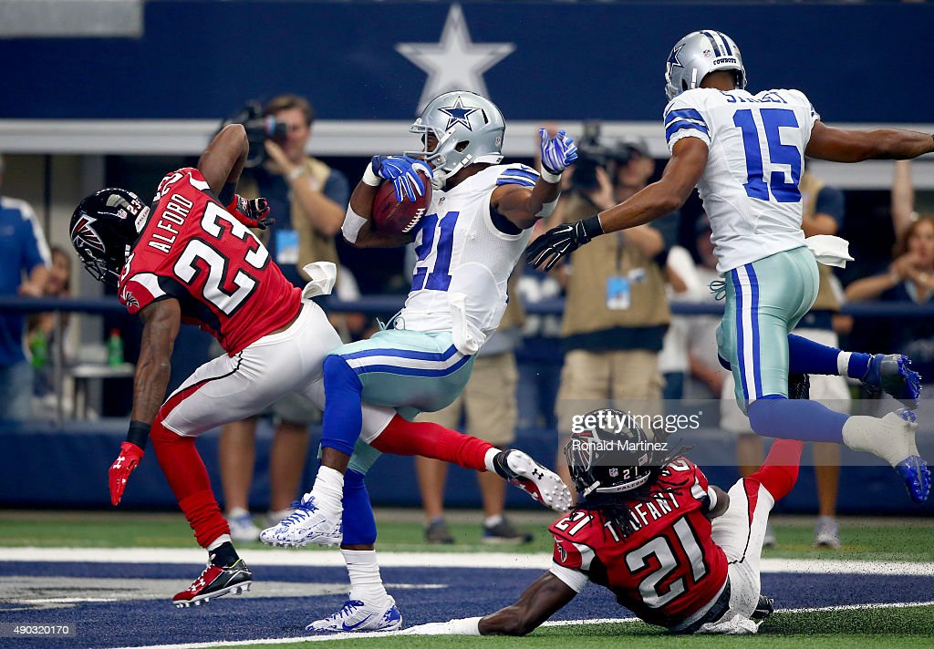 Joseph Randle #21 of the Dallas Cowboys crosses the goal line to score a touchdown between Robert Alford #23 and Desmond Trufant #21 of the Atlanta Falcons as Devin Street #15 of the Dallas Cowboys follows in the first quarter at AT&T Stadium on September 27, 2015 in Arlington, Texas.