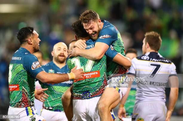 Joseph Tapine is congratulated by Jordan Rapana and Elliot Whitehead of the Raiders after scoring during the round 17 NRL match between the Canberra...