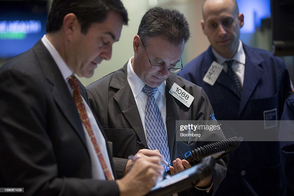 Joseph Tarangelo, a trader with Direct Access Partners LLC, center, works on the floor of the New York Stock Exchange (NYSE) in New York, U.S., on Monday, Jan. 7, 2013. U.S. stocks fell, after the Standard & Poor's 500 Index climbed to a five-year high, as investors awaited the start of the corporate earnings season tomorrow. Photographer: Scott Eells/Bloomberg via Getty Images