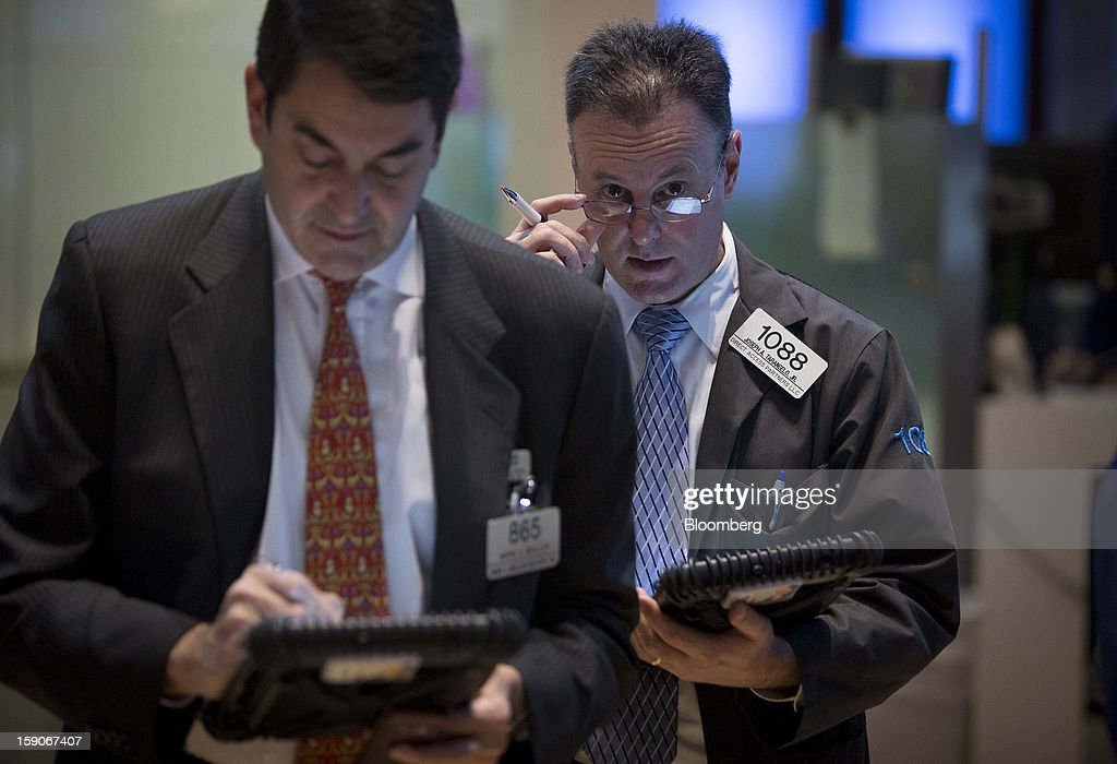 Joseph Tarangelo, a trader with Direct Access Partners LLC, right, works on the floor of the New York Stock Exchange (NYSE) in New York, U.S., on Monday, Jan. 7, 2013. U.S. stocks fell, after the Standard & Poor's 500 Index climbed to a five-year high, as investors awaited the start of the corporate earnings season tomorrow. Photographer: Scott Eells/Bloomberg via Getty Images