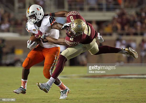 Joseph Yearby of the Miami Hurricanes is tackled by Jalen Ramsey of the Florida State Seminoles during a game at Doak Campbell Stadium on October 10...