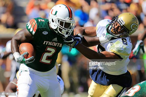 Joseph Yearby of the Miami Hurricanes stiff arms Lamont Simmons of the Georgia Tech Yellow Jackets on a run during the first half at Bobby Dodd...