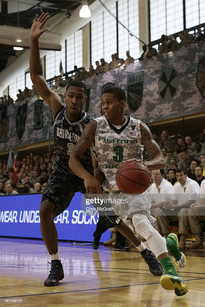 Joseph Young #3 of the Oregon Ducks drives past <a gi-track='captionPersonalityLinkClicked' href=/galleries/search?phrase=Mikael+Hopkins&family=editorial&specificpeople=6753587 ng-click='$event.stopPropagation()'>Mikael Hopkins</a> #3 of the Georgetown Hoyas during the Armed Forces Classic at United States Army Garrison-Humphreys on November 9, 2013 in Pyeongtaek, South Korea.