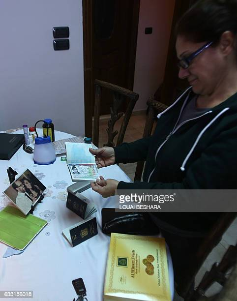 Josephine Abu Assaleh stands in her home in Damascus on January 30 2017 looking at the American visa in her passport that was cancelled following US...
