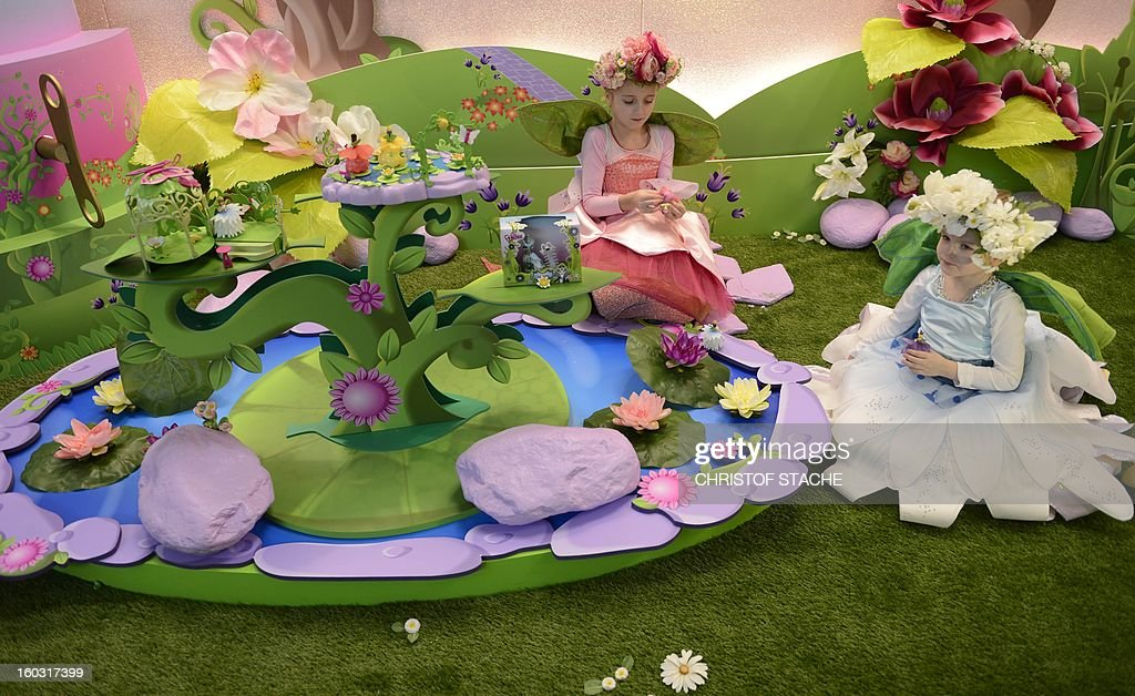 Josephine and Maja play with new flower fairy dolls at a booth during the press preview of the international toy fair in Nuremberg, southern Germany, on January 29, 2013. Around 2.700 exhibitors show more than 1 million products at the international toy fair which opens its doors from January 29 to February 4, 2013. AFP PHOTO / CHRISTOF STACHE