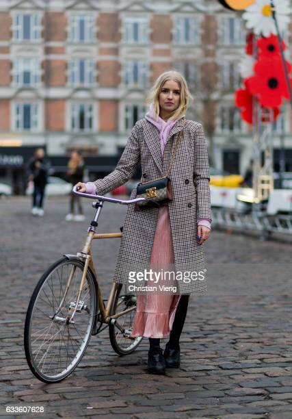 Josephine Bredsted with her bike wearing a Gucci bag pink hoody checked coat salmon coloured dress during the Copenhagen Fashion Week Autumn/Winter...