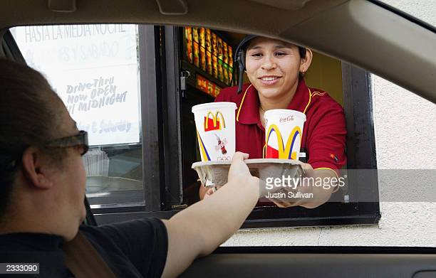 Josephine Hernandez hands a tray of drinks to a drive thru customer at a McDonald's restaurant July 29 2003 in Redwood City California McDonald's...