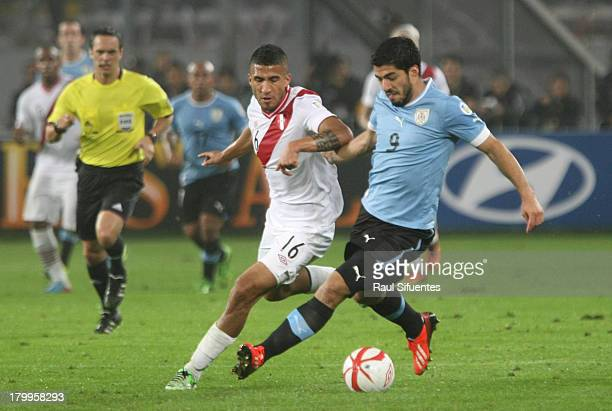 Josepmir Ballon of Peru fights for the ball with Luis Suarez of Uruguay during a match between Peru and Uruguay as part of the 15th round of the...
