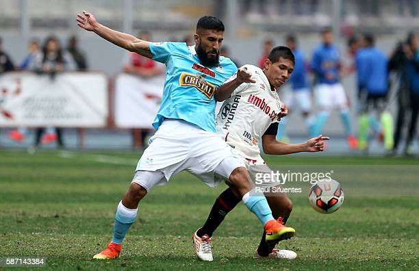 Josepmir Ballon of Sporting Cristal struggles for the ball with Edison Flores of Universitario during a match between Universitario and Sporting...