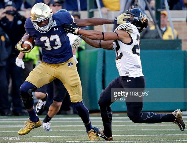 Josh Adams of the Notre Dame Fighting Irish stiff arms Ryan Janvion of the Wake Forest Demon Deacons on his 98yard rushing touchdown during the...