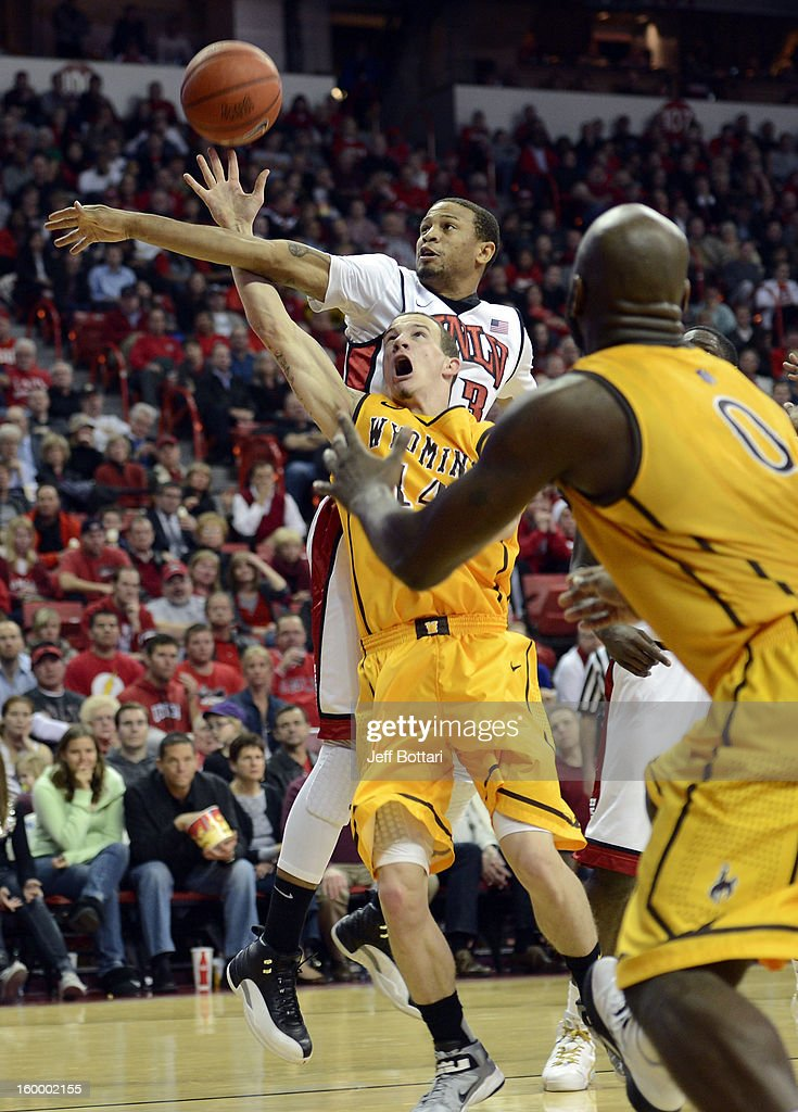 Josh Adams #14 of the Wyoming Cowboys gets fouled by Bryce Dejean-Jones #13 of the UNLV Rebels at the Thomas & Mack Center January 24, 2013 in Las Vegas, Nevada. The Rebels won 62-50.