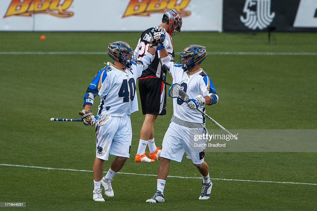 Josh Amidon #9 and <a gi-track='captionPersonalityLinkClicked' href=/galleries/search?phrase=Matt+Danowski&family=editorial&specificpeople=4183765 ng-click='$event.stopPropagation()'>Matt Danowski</a> #40 of the Charlotte Hounds celebrate a Danowski goal in the first half of a Major League Lacrosse game at Sports Authority Field at Mile High on June 29, 2013 in Denver, Colorado. The Outlaws led the Hounds 10-5 at the half.