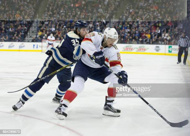 Josh Anderson of the Columbus Blue Jackets and Aleksander Barkov of the Florida Panthers battle for the puck during the third period of the game...