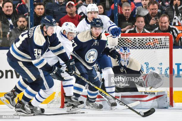 Josh Anderson of the Columbus Blue Jackets and Ryan Murray of the Columbus Blue Jackets help goaltender Joonas Korpisalo of the Columbus Blue Jackets...