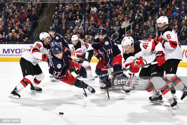 Josh Anderson of the Columbus Blue Jackets falls to the ice while skating after a loose puck with Sami Vatanen of the New Jersey Devils during the...