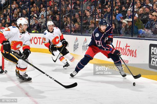 Josh Anderson of the Columbus Blue Jackets keeps the puck from Mark Jankowski of the Calgary Flames during the first period of a game on November 22...