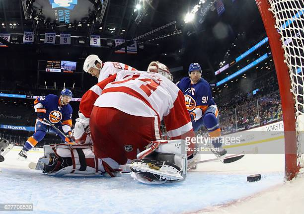 Josh Bailey and John Tavares of the New York Islanders converge on Petr Mrazek of the Detroit Red Wings during the first period at the Barclays...