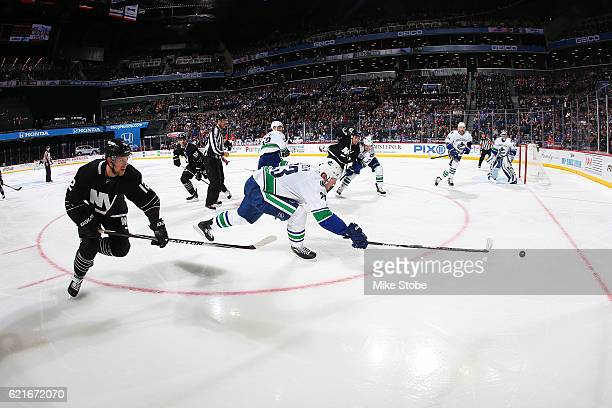 Josh Bailey of the New York Islanders and Alexander Edler of the Vancouver Canucks pursue the loose puck at the Barclays Center on November 7 2016 in...